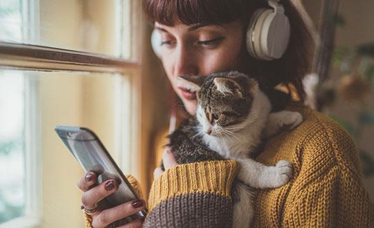 owner holding kitten while listening to music on headphones