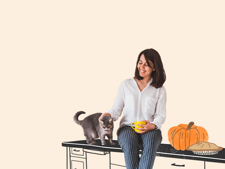Woman on table with cat and pumpkin